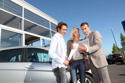 Tre persone consultano un documento davanti a un'automobile