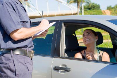 uomo in divisa notifica verbale di multa a una donna in auto