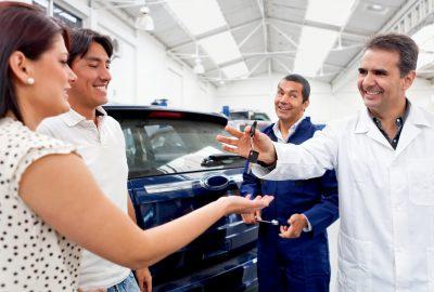 Uomo consegna chiavi auto a una coppia