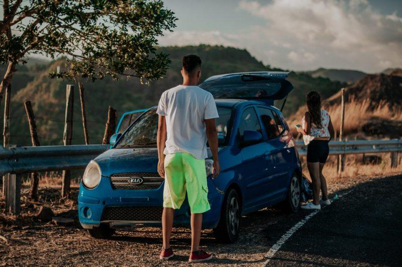 ragazzo di spalle davanti a una macchina e a una ragazza