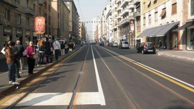 corsia preferenziale e persone in attesa su un marciapiede