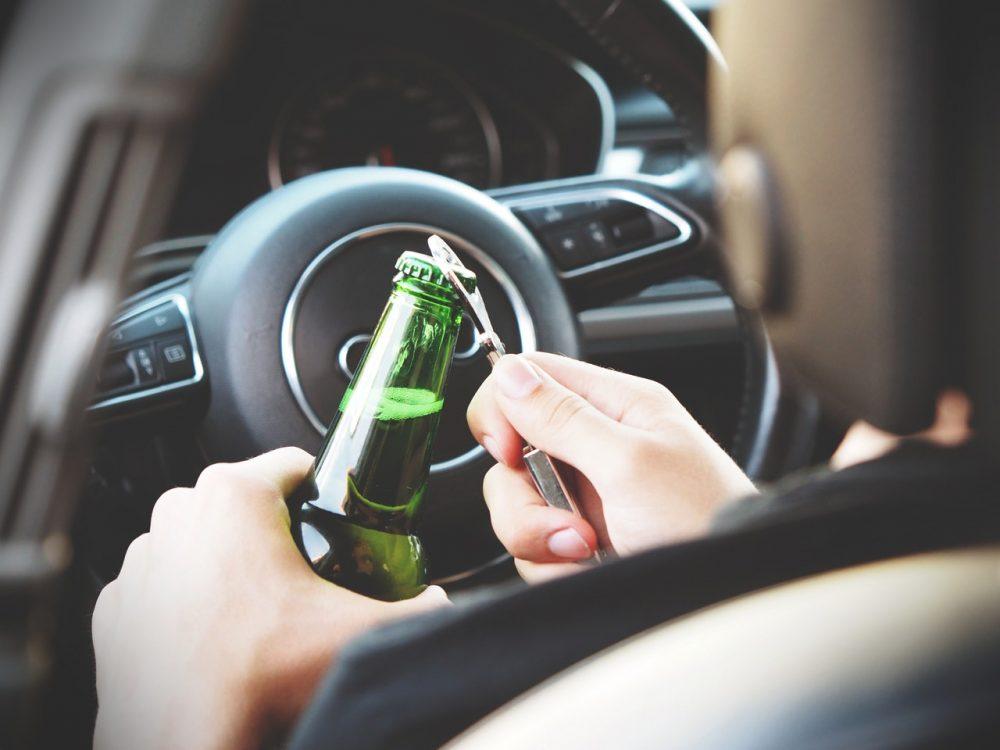 mano che apre bottiglia di birra in un'automobile