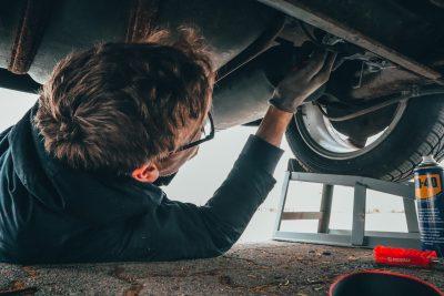 uomo al lavoro sotto un'automobile