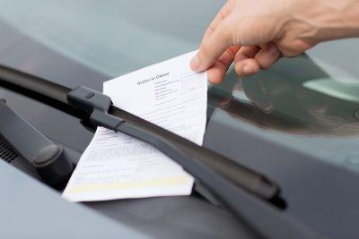 mano che preleva una multa dal lunotto di un'automobile